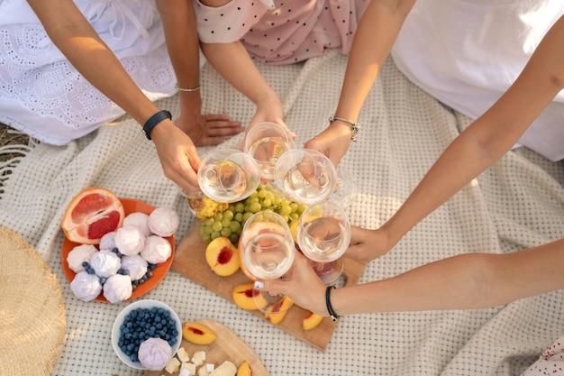 Gezelschap van vrouwelijke vrienden geniet van een zomerpicknick en hef glazen met wijn Premium Foto
