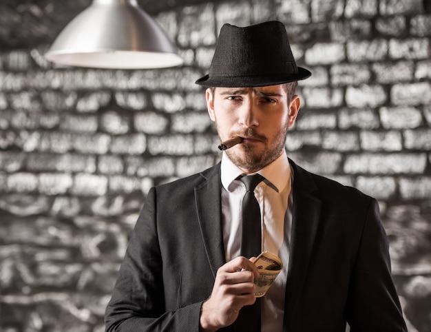 Gezicht op een gangster man rookt een cubaanse sigaar. Premium Foto
