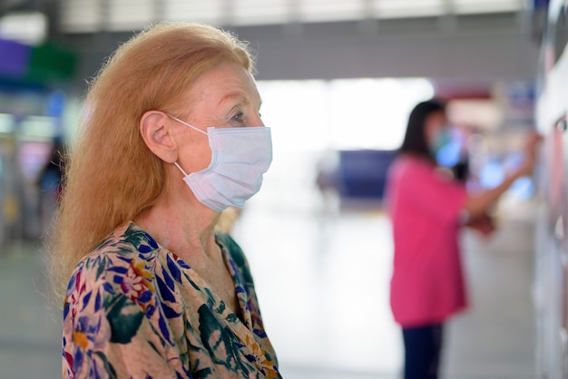 Gezicht van blonde hogere vrouw die met masker kaartje kopen bij het hemelstation Premium Foto