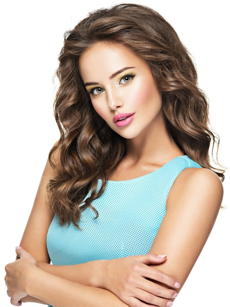 Gezicht van de mooie sensuele vrouw met lang krullend haar. vrij jong meisje met maniersamenstelling. model vormt op witte achtergrond Gratis Foto