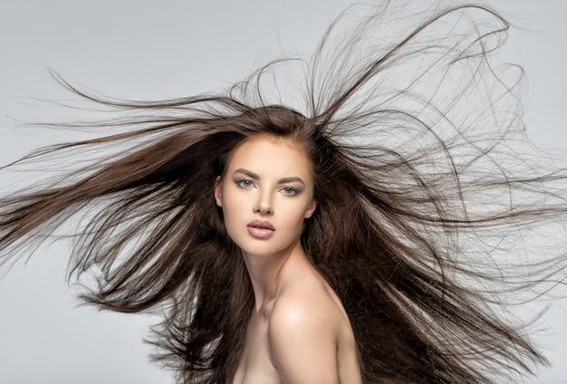Gezicht van de mooie vrouw met lang bruin haar poseren in de studio Gratis Foto