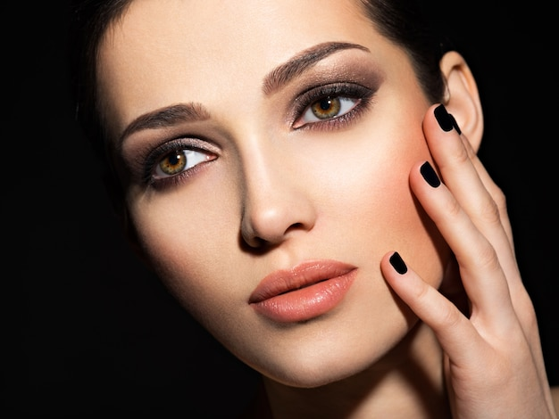 Gezicht van een mooi meisje met mode make-up en zwarte nagels poseren in studio over donkere achtergrond Gratis Foto