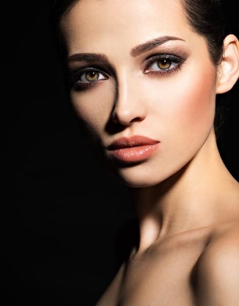 Gezicht van een mooi meisje met rokerige ogen make-up poseren in studio over donkere achtergrond Gratis Foto