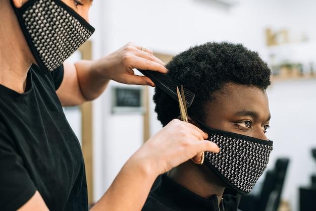 Gezicht van een zwarte man die een knipbeurt krijgt in een kapsalon met een zwart masker op zijn gezicht van het coronavirus. Premium Foto