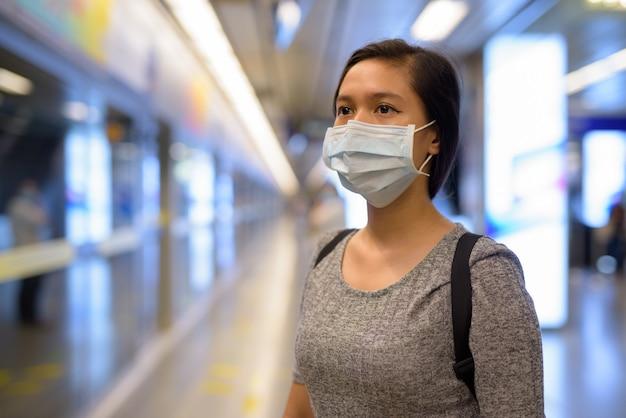 Gezicht van jonge aziatische vrouw met masker voor bescherming tegen uitbraak van coronavirus te wachten op het metrostation Premium Foto