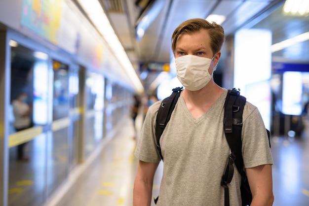 Gezicht van jonge man met masker voor bescherming tegen uitbraak van coronavirus te wachten op het metrostation Premium Foto