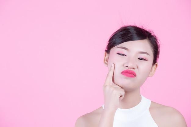 Gezichtshuidproblemen vrouwen - ongelukkige jonge vrouwen die haar huid op een roze achtergrond raken. Gratis Foto
