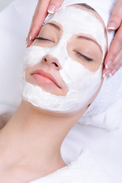 Gezichtsmasker voor jonge vrouw in de salon van schoonheidsclose-up Gratis Foto