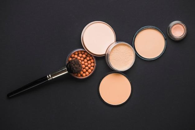 Gezichtspoeder; bronzing parels en make-up borstel op zwart oppervlak Gratis Foto