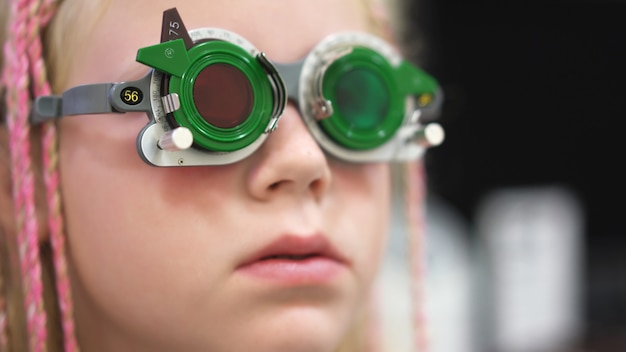Gezichtsvermogen controleren. kaukasisch meisje met visuele handicaps. medische behandeling en revalidatie Premium Foto