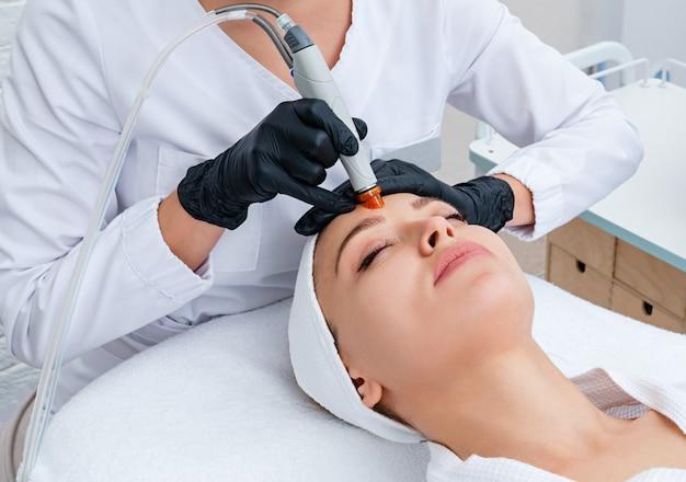 Gezichtsverzorging. close-up van vrouwengezicht reiniging bij cosmetology-kliniek, het stofzuigen Premium Foto