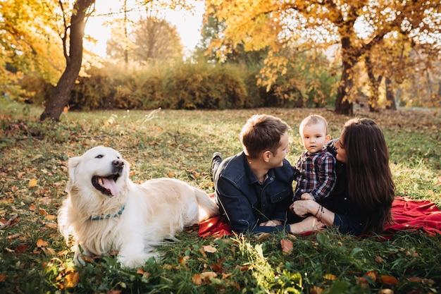 Gezin met een kind en een golden retriever in een herfst park Premium Foto