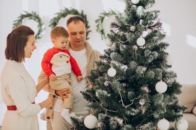 Gezin met zoontje op kerstmis door kerstboom thuis Gratis Foto