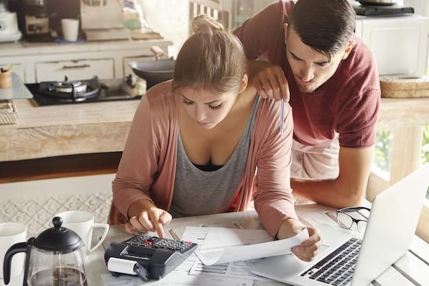 Gezinsbudget en financiënconcept. jonge ernstige vrouw en echtgenoot die rekeningen thuis samen doen Gratis Foto