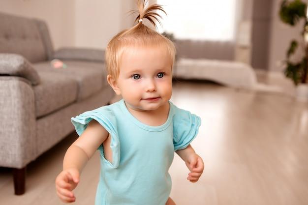 Gezond babymeisje in een kamer naast een grijze bank leert lopen Premium Foto