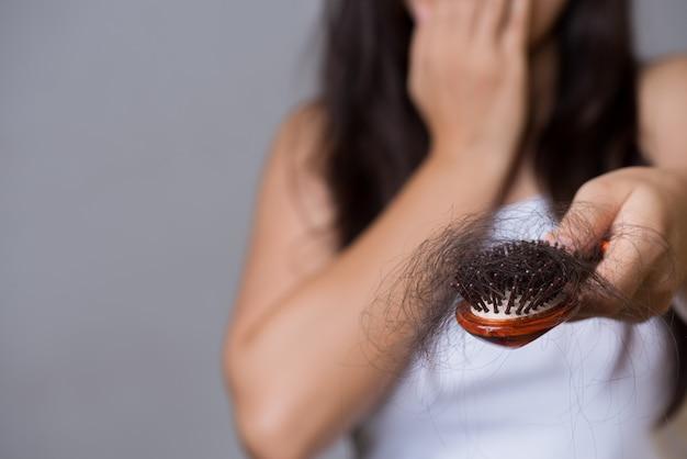 Gezond concept. de vrouw toont haar borstel met lang verlieshaar Premium Foto