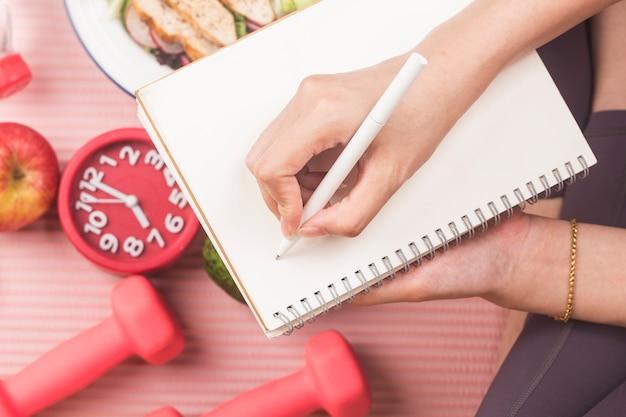 Gezond concept met voedingsvoedsel in lunchdoos en geschiktheidsmateriaal met vrouw die tijd schrijft om gezond te worden op dagboekboek Premium Foto