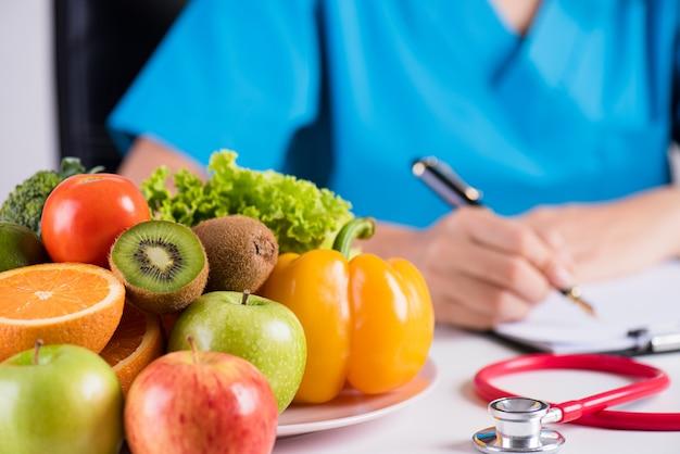 Gezond concept, verse groenten en fruit met stethoscoop die op het bureau van de arts liggen. Premium Foto