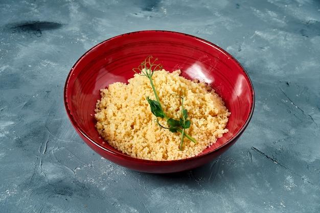 Gezond en dieetbijgerecht - couscouspap in een bordeauxrode kom op een concrete oppervlakte Premium Foto