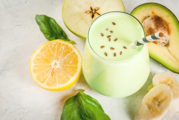 Gezond eten. dieetontbijt of snack. groene smoothies van yoghurt, avocado, banaan, appel, spinazie en citroen. op witte betonnen stenen tafel, met ingrediënten. kopieer ruimte Premium Foto