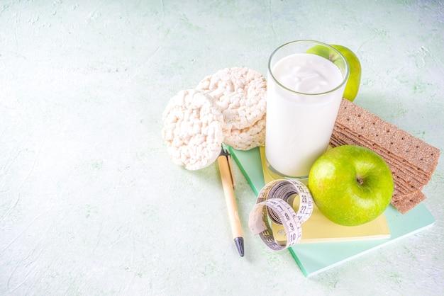 Gezond eten en gewichtsverlies concept. appel, yoghurt, gezond ontbijtgranen knäckebröd, notitieboekje en meetlint op lichtgroene muur kopie ruimte voor tekst Premium Foto