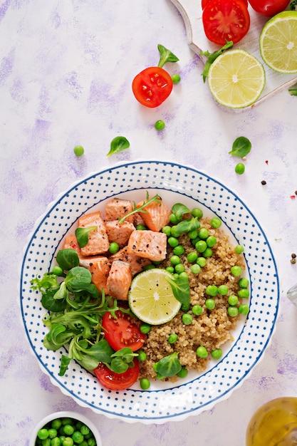 Gezond eten. plakjes gegrilde zalm, quinoa, groene erwten, tomaat, limoen en slablaadjes. plat leggen. bovenaanzicht Premium Foto