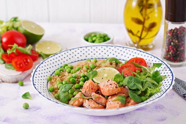 Gezond eten. plakjes gegrilde zalm, quinoa, groene erwten, tomaat, limoen en slablaadjes Premium Foto