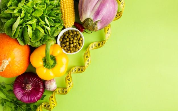 Gezond groentenhoogtepunt van vitaminen op groene achtergrond Gratis Foto