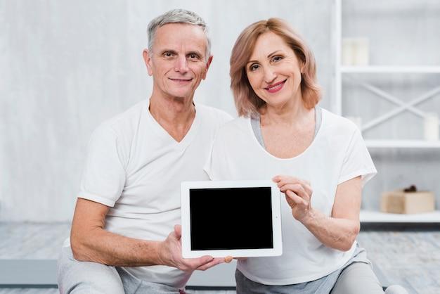 Gezond hoger paar die camera bekijken die digitale tablet met het zwarte scherm houden Gratis Foto