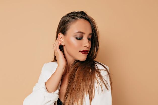 Gezond huid vrouwelijk concept, mooie vrouw met wijnstoklippen en donkere ogen die witte jas dragen die op beige muur stellen. jonge vrouw lachend natuurlijk portret, mooi vrouwelijk meisje met lang haar Gratis Foto
