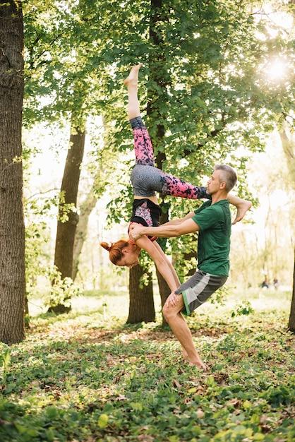 Gezond medio volwassen paar dat acrobatische yogatraining in park doet Gratis Foto
