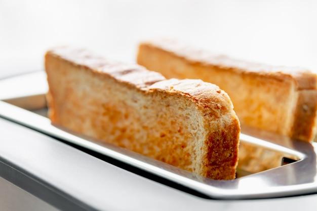 Gezond modevoedsel van ontbijt. roosteren in een broodrooster. broodrooster met smakelijke ontbijttoosts op de lijst Premium Foto