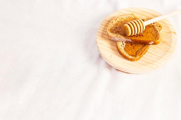 Gezond natuurlijk honing en brood in plaat over witte doek Gratis Foto
