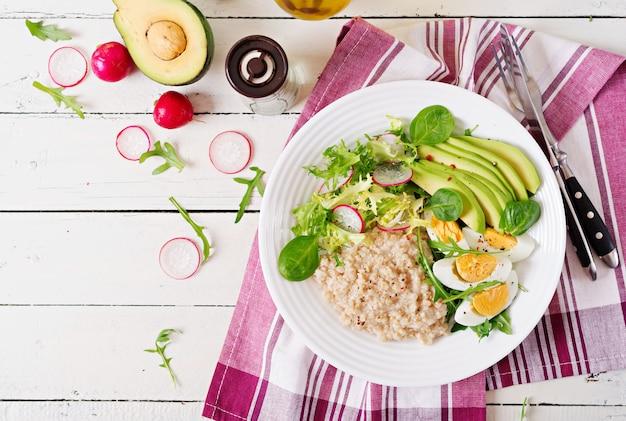 Gezond ontbijt. dieet menu. havermoutpap en avocadosalade en eieren. bovenaanzicht Premium Foto