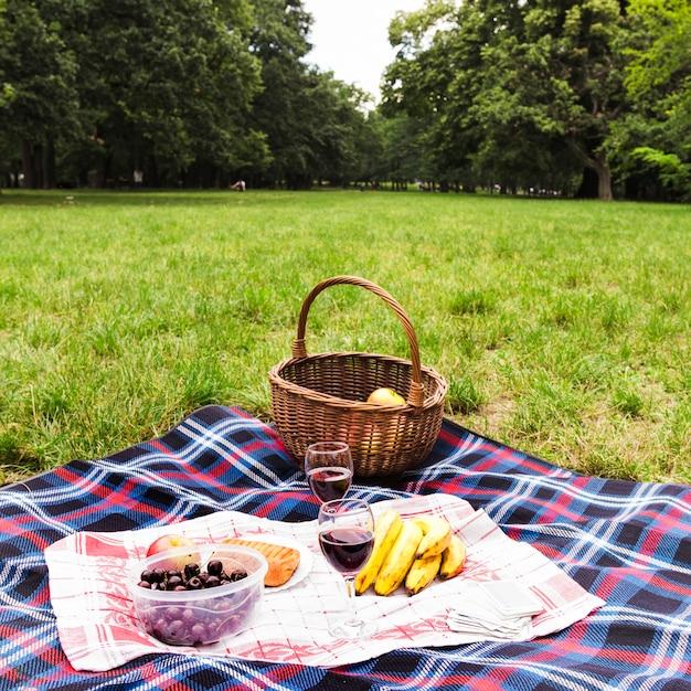 Gezond ontbijt en wijnglazen op deken over het groene gras Gratis Foto