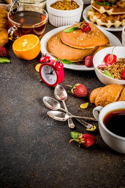 Gezond ontbijt eten concept, verschillende ochtend eten - pannenkoeken, wafels, croissant havermout sandwich en muesli met yoghurt, fruit, bessen, koffie, thee, jus d'orange Premium Foto
