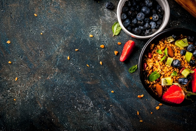 Gezond ontbijt met muesli of granola met noten en verse bessen en fruit Premium Foto