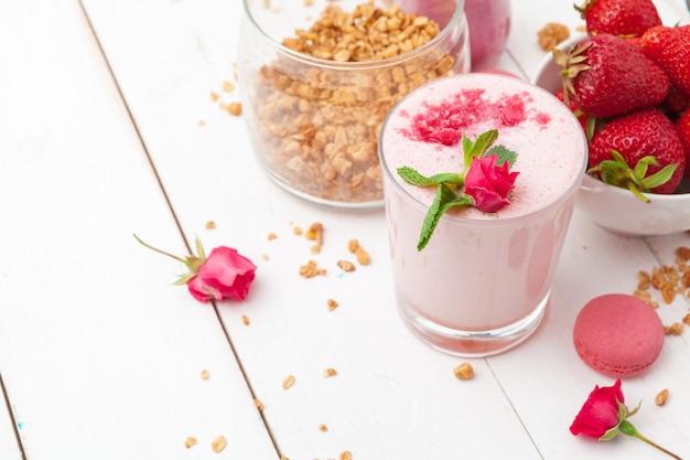 Gezond ontbijt met yoghurt, granola en aardbeien op wit hout Premium Foto