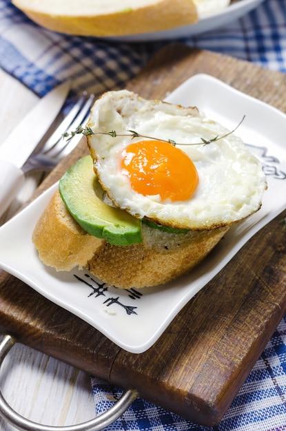 Gezond ontbijt. sandwich met roggebrood, avocado en gebakken eieren. Premium Foto
