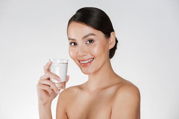 Gezond portret van jonge gelukkige vrouw met haar in broodje dat nog water van transparant glas drinkt, dat over wit wordt geïsoleerd Gratis Foto