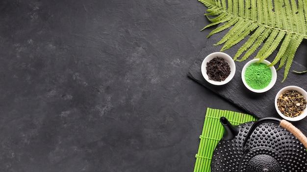 Gezond theeingrediënt met zwarte theepot en varenbladeren over achtergrond Gratis Foto