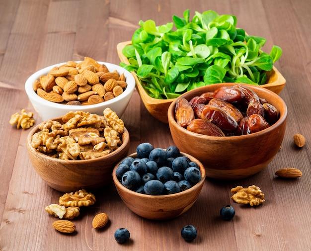 Gezond veganistisch voedsel - droge vruchten, greens, noten, bes. superfoods Premium Foto