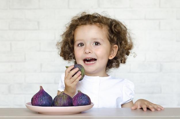 Gezond voedselconcept. gelukkig kind plezier eten van verse vijgen. meisje geniet van het hebben van de juiste, goede snack. kid houdt van bessen en fruit. herfst oogst Premium Foto