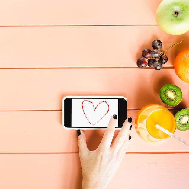 Gezond voedselconcept met smartphone en vruchten Gratis Foto