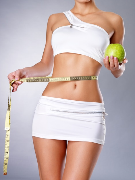 Gezond vrouwelijk lichaam met appel en meetlint. gezond fitness en eetlevensstijlconcept. Gratis Foto