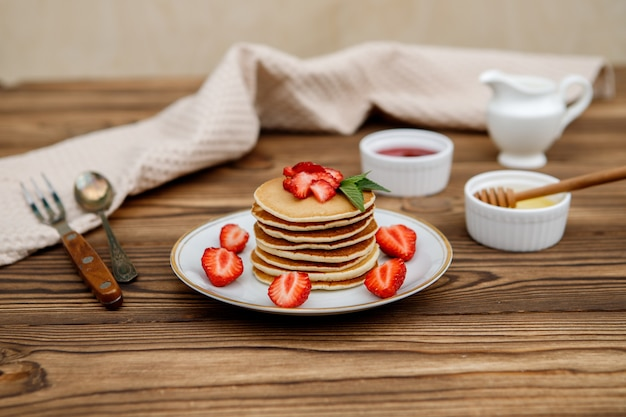 Gezond zomerontbijt, zelfgemaakte klassieke amerikaanse pannenkoeken met verse bessen en honing op een houten achtergrond. heerlijke gebakjes, dessert. Premium Foto