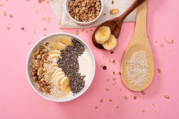 Gezonde ananas, mango smoothie bowl met kokos, bananen, bosbessen en granola. bovenaanzicht scène op een heldere Premium Foto