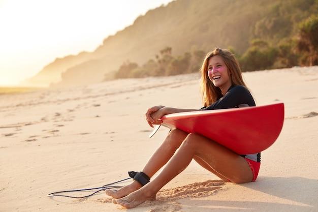 Gezonde atletische vrouw met gelukkige uitdrukking, heeft slanke benen, geniet van recreatie en surfen aan de leiband Gratis Foto