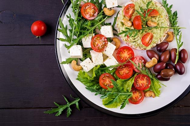 Gezonde avocadotoosts voor ontbijt, guacamole, kalamataolijven, tomaten, cashewnoten en feta-kaas Premium Foto