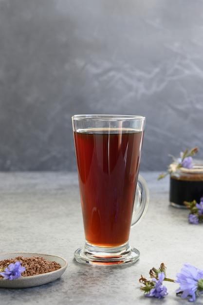 Gezonde cichoreidrank als koffie in glas en frisse zomerblauwe bloemen. onmiddellijk en geconcentreerd. verticaal. detailopname. Premium Foto